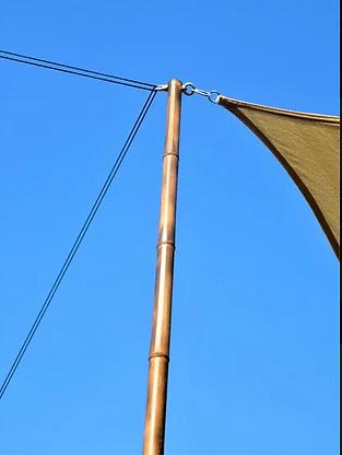 Poteau en bambou coloré à la flamme pour accrocher une toile tendue.