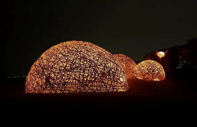 Photo de nuit de plusieurs dômes en bambou éclairés de l'intérieur.